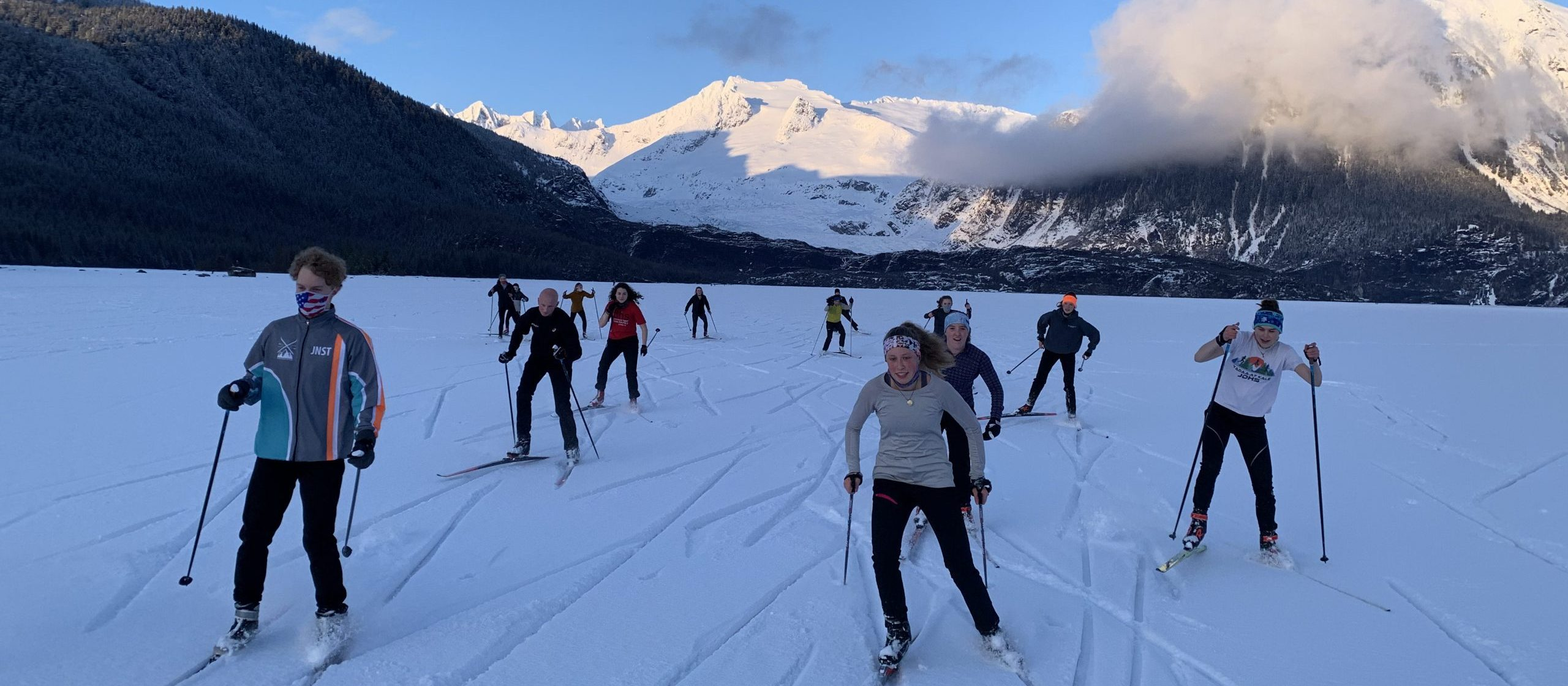 high school skiers pose in front of a snowy John Muir Cabin